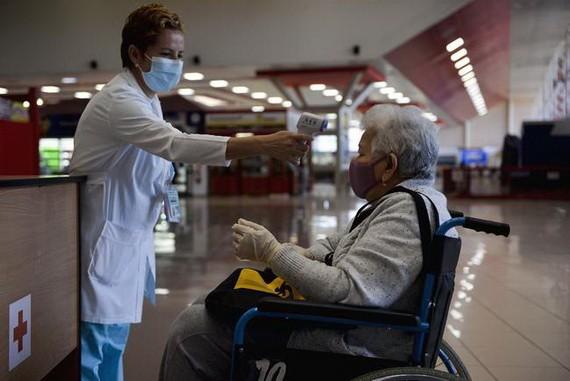 古巴首都哈瓦那何塞·馬蒂國際機場工作人員(左)為入境旅客測量體溫。(圖源:互聯網)