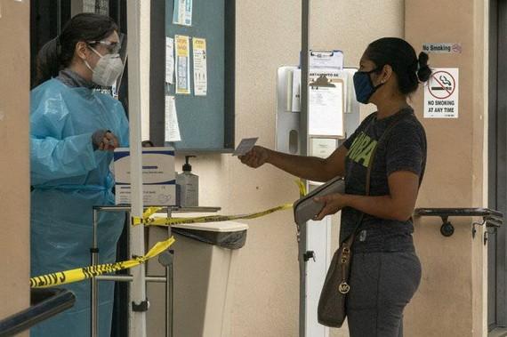 7月26日,一名病人在美國洛杉磯向護士出示她的疫苗接種卡。(圖源:新華社)