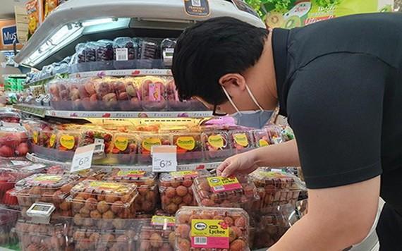 新加坡消費者在超市選購越南荔枝。(圖源:VNA)