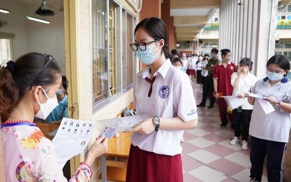 圖為2021年7月7日全國舉辦第一次高中畢業試首日,監考老師對考生步入考室前進行核對證件。(圖源:獨立)