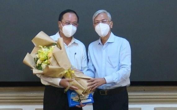 阮玉強同志(左)從市人委會副主席武文歡手中接過委任《決定》和祝賀鮮花。(圖源:廷李)