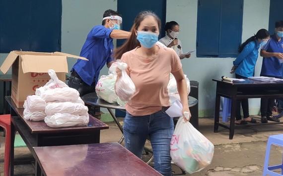 一名貧困勞工領取必需品後趕快回租房去。