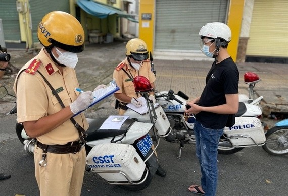 一名違反防疫規定的男性被交警截停進行筆錄並開具罰單。(圖源:VTC News)