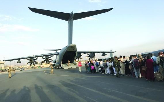 人們在喀布爾國際機場排隊等候乘坐德國軍用飛機離開。(圖源:互聯網)