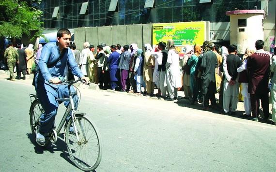 人們在阿富汗喀布爾一家銀行外排隊。(圖源:互聯網)
