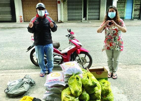 何麗娟(右)把救濟品轉交某單位負責人。