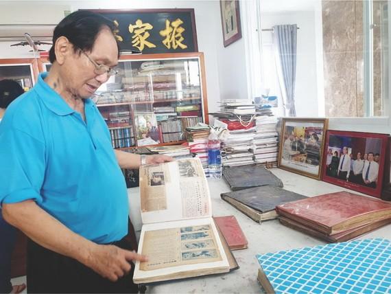 張漢明書畫家在整理剪報冊。