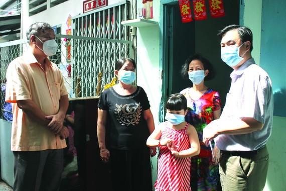 市民族處副主任曾福祿(右一)和第十郡人委會副主席裴世海(左一)向一華人戶贈送資助金。