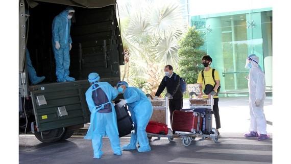 Các công dân Việt Nam trở về từ  Singapore được kiểm tra y tế, đưa đi cách ly theo quy định