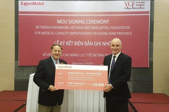 Đại diện lãnh đạo ExxonMobil trao bảng tài trợ cho đại diện Quỹ tài trợ VinaCapital. Ảnh: NGUYÊN KHÔI