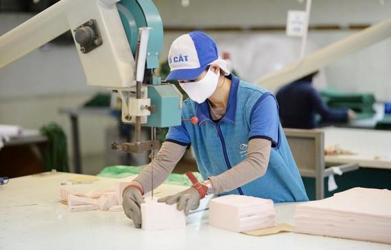 Công nhân tại Công ty Dệt kim Đông Xuân tăng công suất cắt may khẩu trang để đáp ứng nhu cầu mua khẩu trang giá bình ổn của người dân cả nước. Ảnh: Vinatex