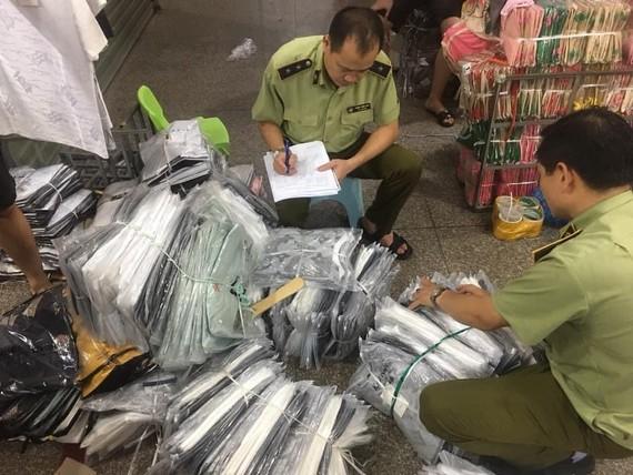 Cán bộ QLTT kiểm kê các lô hàng thời trang nhái, lậu trong chợ Ninh Hiệp hôm 4-6
