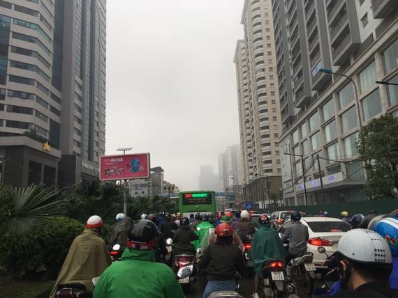 Sáng nay 1-3, Hà Nội tắc đường, mưa bụi, khói sương vì thời tiết giao mùa. Ảnh: VĂN PHÚC