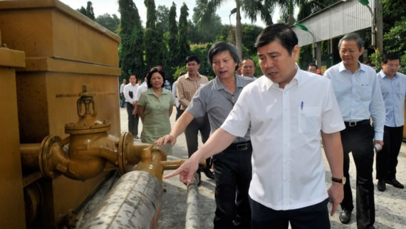 Chairman Nguyen Thanh Phong sees made in Vietnam gasification furnace, a technology that turns trash into a fuel, at Go Cat landfill site (Photo: SGGP)