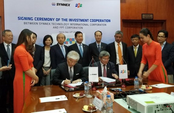 FPT director general Bui Quang Ngoc and director general of Synnex Evans Tu sign the investment cooperation (Photo: SGGP)