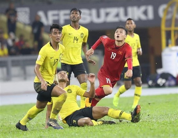 Nguyen Quang Hai (shirt no.19) is surrounded by Malaysian players (Source: VNA)