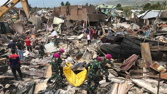 Rescuers seek survivors in the rubble in the aftermath of an earthquake and tsunami in Indonesia last year (Photo: EPA)