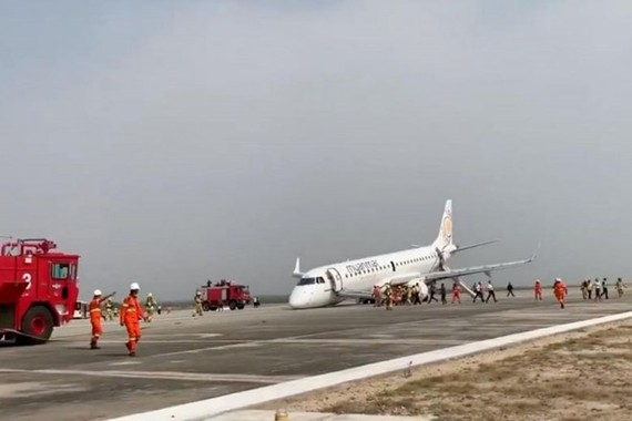 A passenger records the scene on her phone as firefighters attend to the scene after Myanmar Airlines flight UB103 landed without a front wheel at Mandalay International Airport (Photo: REUTERS)