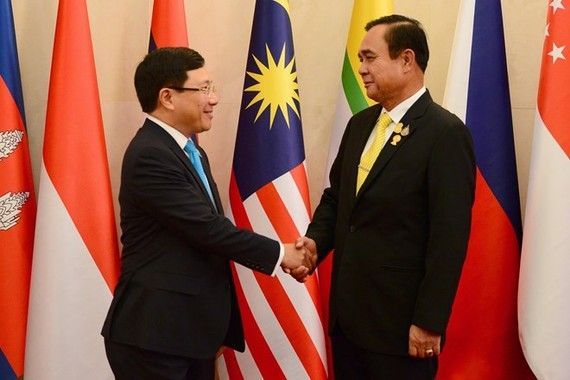 Vietnamese Deputy Prime Minister and Foreign Minister Pham Binh Minh (L) shakes hands with Thai Prime Minister Prayut Chan-o-cha at the meeting in Bangkok on July 31 (Photo: VNA)