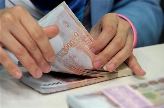 The baht notes are counted at the Krungthai Bank in Bangkok (Illustrative image. Photo: AFP/VNA)