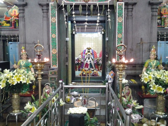 In the center is the shrine of the Goddess Mariamman and in a relief above the shrine the goddess is seated with the gods Ganesha and Naaga on either side.