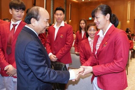 Prime Minister Nguyen Xuan Phuc shakes hands with swimmer Nguyen Thi Anh Vien (right) who wins six gold medals at the 30th SEA Games in the Philippines (Photo: VGP)