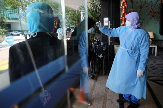 A nurse checks the temperature of a visitor as part of the coronavirus screening procedure at a hospital in Kuala Lumpur on Feb 3, 2020. (Photo: Reuters)