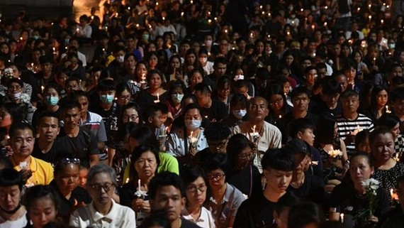 People take part in a candle-lit vigil for victims following the mass shooting in Nakhon Ratchasima (Source: AFP)