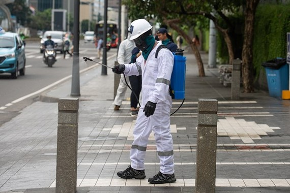 A worker fumigates the pavement in Jakarta, Indonesia, on March 19 in a bid to prevent the spread of the novel coronavirus (Photo: Xinhua/VNA)