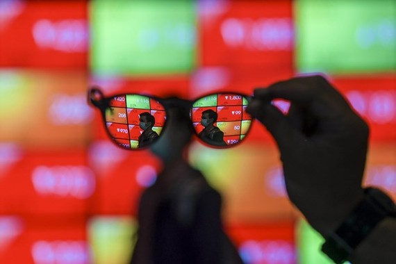 Employees pass a screen displaying stock movements at the Indonesia Stock Exchange building in Jakarta on March 2, 2020. (Photo: Antara)