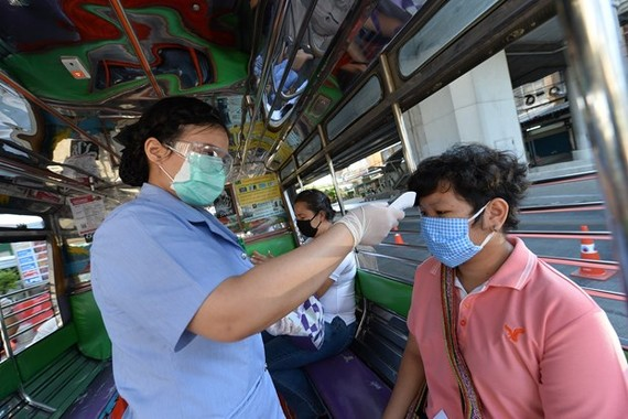 A health worker examines a person's body temperature at a checkpoint in Bangkok, Thailand, on March 26 (Photo: Xinhua/VNA)
