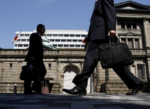 Japanese office workers walk on a street in front of the Bank of Japan headquarters in Tokyo. (Photo: Reuters)
