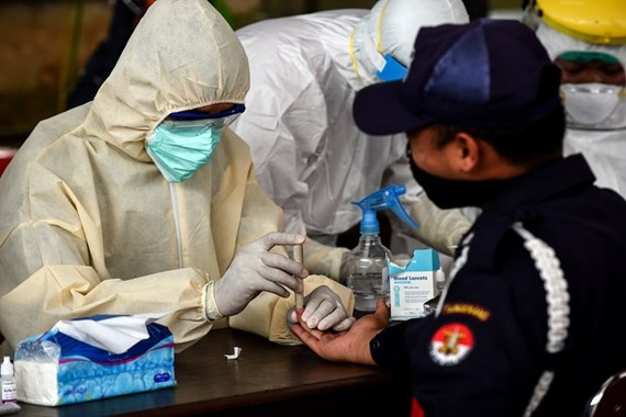 A man has his blood sample taken for rapid COVID-19 testing in South Tangerang, Indonesia's Banten province, on April 21 (Photo: Xinhua/VNA)