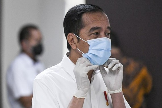 President Joko Widodo adjusts his face mask while visiting COVID-19 patients (Photo: AFP)
