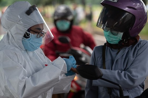A health worker takes a motorcyclist's blood sample for COVID-19 testing in Tangerang city, Indonesia, on May 4 (Photo: AFP/VNA)