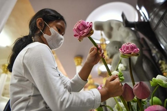 A young student is placing flowers at an altar in a Buddhist pagoda in Phnom Penh. (Photo: AFP)