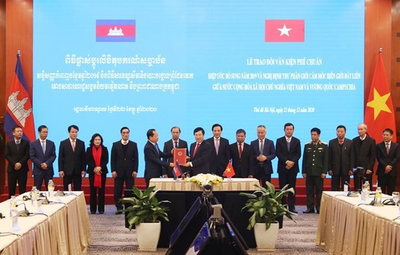 Deputy Prime Minister and Minister of Foreign Affairs Pham Binh Minh (front, right) hands over the ratification document to Cambodian Ambassador Chay Navuth in Hanoi on December 22 (Photo: VNA)