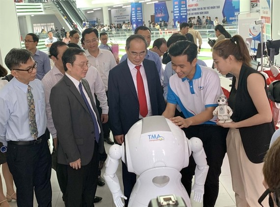 """HCMC leaders look at AI products displayed at an exhibition held on the """"Day for AI and IT Enterprises"""" event recently in HCMC. (Photo: VNA/VNS)"""