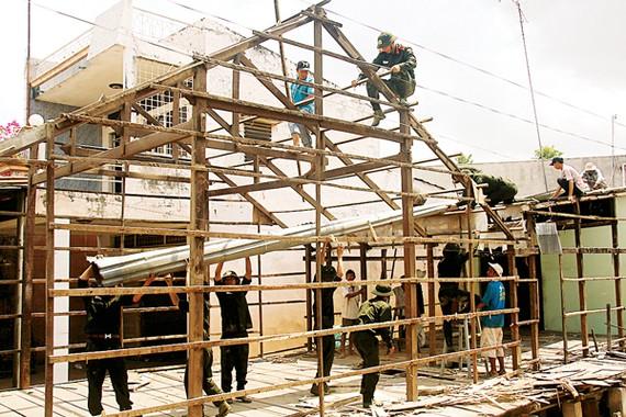 Lực lượng chức năng cùng người dân xã Mỹ Hội Đông, huyện Chợ Mới (An Giang) tháo dỡ nhà tại khu vực sạt lở