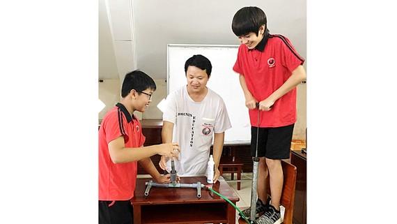 Thầy Nguyễn Tường Vũ (giữa)  và học sinh tại phòng thí nghiệm Vật lý của Trường quốc tế Phượng Hoàng