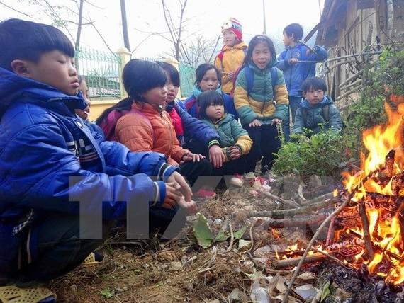 Học sinh trường tiểu học Yên Lạc, huyện Nguyên Bình (Cao Bằng) co ro bên đống lửa. Ảnh: Quốc Đạt/TTXVN