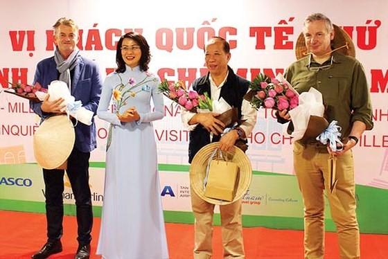 Phó Chủ tịch UBND TPHCM Nguyễn Thị Thu tặng hoa chúc mừng các du khách quốc tế tại lễ đón khách du lịch thứ 5 triệu đến TPHCM