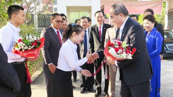 Học sinh Trường PTTH Hữu nghị Viêng Chăn - TPHCM tặng hoa, chào đón đoàn. Ảnh: KIỀU PHONG