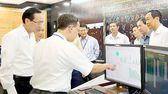 Đồng chí Lê Thanh Liêm nghe các nhân viên trực vận hành tại Trung tâm Điều độ hệ thống điện TPHCM báo cáo tình hình