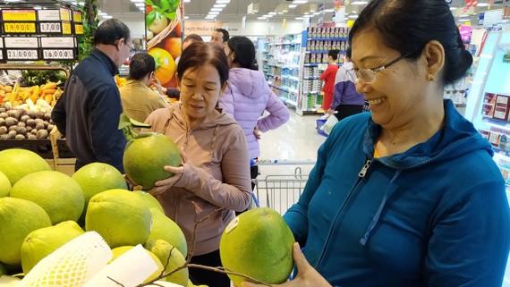 Khách hàng chọn mua trái cây bình ổn giá tại siêu thị Co.opmart                Ảnh: CTV