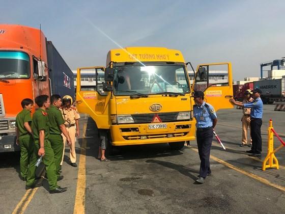 Lực lượng tiến hành kiểm tra hàng chục tài xế ra vào cảng Cát Lái, quận 2. Ảnh: CHÍ THẠCH
