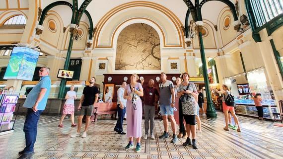 Đông đảo du khách  nước ngoài say sưa  xem một di sản  kiến trúc tại TPHCM. Ảnh: HOÀNG HÙNG