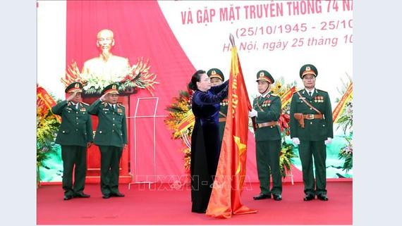 Chủ tịch Quốc hội Nguyễn Thị Kim Ngân gắn Huy hiệu Anh hùng LLVT lên lá cờ truyền thống của Tổng cục II. Ảnh: TTXVN