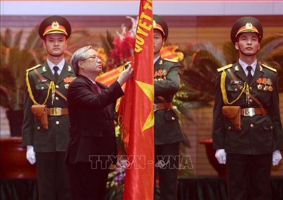 Đồng chí Trần Quốc Vượng, Thường trực Ban Bí thư gắn Huân chương Bảo vệ Tổ quốc hạng Nhất lên lá cờ truyền thống của Tổng cục Chính trị QĐND Việt Nam. Ảnh: TTXVN