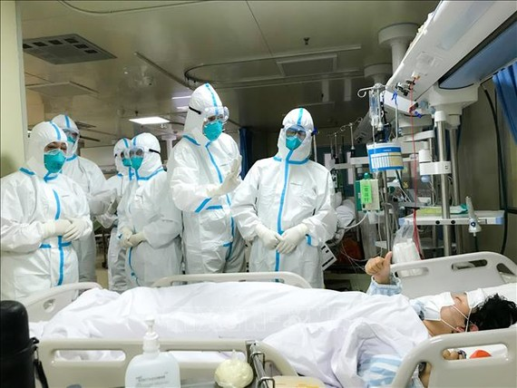 Nhóm bác sĩ bệnh viện Trường đại học quân y số 2 kiểm tra sức khỏe một bệnh nhân tại bệnh viện Hankou ở Vũ Hán, tỉnh Hồ Bắc ngày 27-1. Ảnh: THX/TTXVN